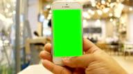 Hand hält smartphone mit Anwendung des berühmten sozialen Netzwerk im Coffee Shop