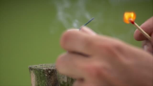 CU Hand igniting firecracker which explodes, Stowe, Vermont, USA