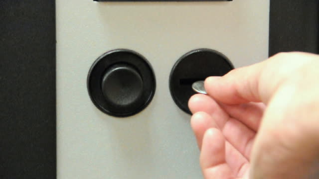 CU Hand inserting coin into vending machine, Los Angeles, California, USA
