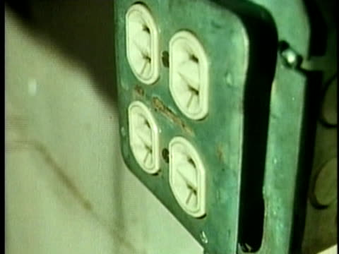 1961 CU Hand inserting two pin plug into socket / United States / AUDIO
