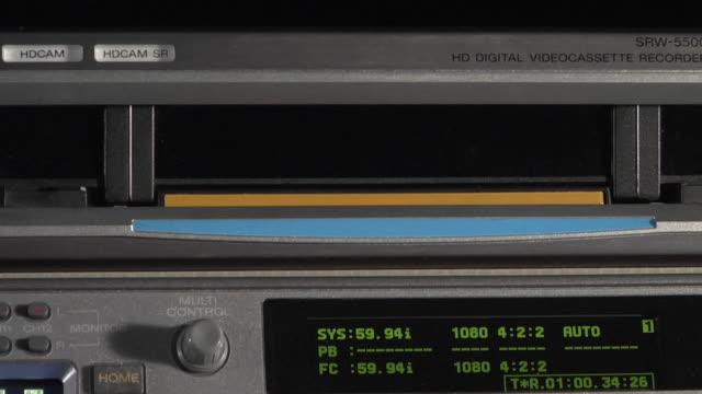 ECU Hand inserting videotape into professional deck / New York City, New York, USA