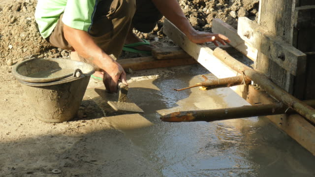 hand of builder worker plastering at floor cement.