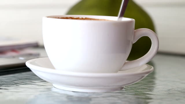 Hand of men use spoon stirred hot coffee in white mug.