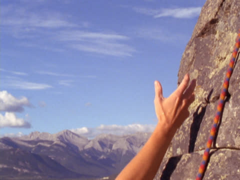 Hand of mountain climber reaching for hand of another