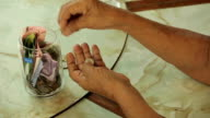 Hand of senior woman counting money with glass bank