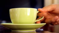 hand picking green cup of coffee on wooden table