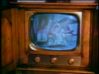 1953 hand picking up small jar on television screen / educational