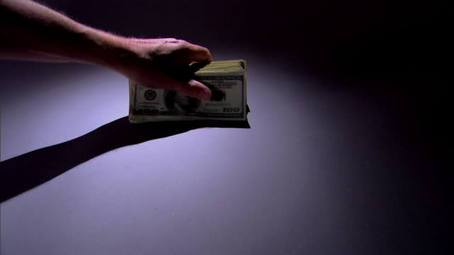 A hand places a stack of money on a spotlighted surface.