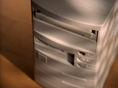 Hand placing CD into CD-ROM drive