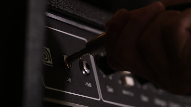 CU of hand plugging and unplugging cord on amplifier