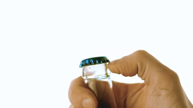 Hand popping open glass bottle