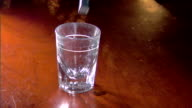 Hand pouring amber liquid into shot glass sitting on wood surface spilling over side Alcohol pub tavern spirits whiskey