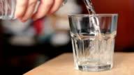 Hand gießen Wasser in Glas trinken