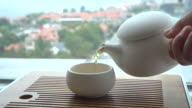 hand pouring tea beside window
