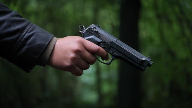 Hand Raising Pistol To Shoot
