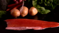 Hand seasoning trout fillet in front of vegetable selection