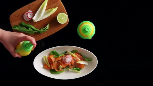 MS Hand setting plate of salmon salad and spraying lemon water on it / Seoul, South Korea