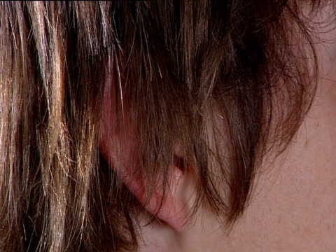 Hand smoothes long hair behind ear