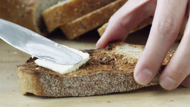 CU Hand spreading butter on toasted bread