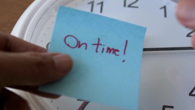hand sticking note paper on clock with word On Time