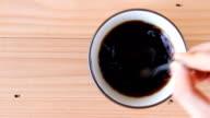hand stir coffee on wooden background