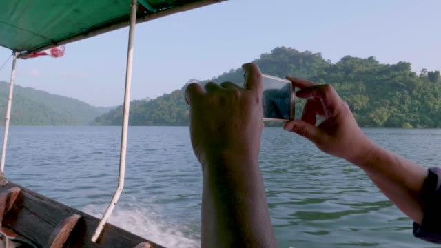 Hand ta ett foto med Smart telefon i thailändska taxibåt