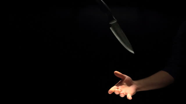 Hand throwing and catching a knife.