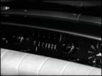 / CU hand tuning 1953 Nash car radio and pushing one button / CU male hand tuning left knob of 1962 Oldsmobile car radio pushing buttons and then...