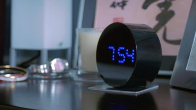 CU Hand turning off alarm clock on bedside table, New York City, New York, USA