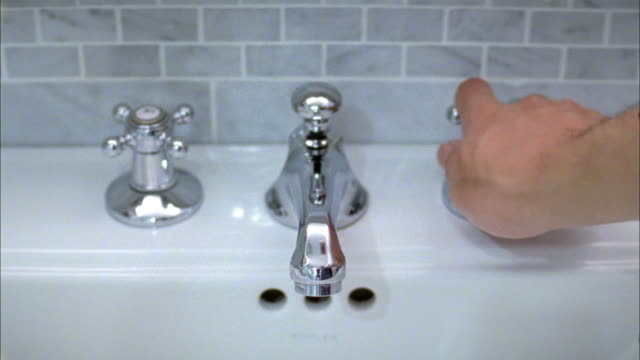 CU Hand turning water on and off at sink, New York City, New York, USA