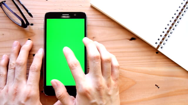 hand using mobile phone with green screen on office table - top view