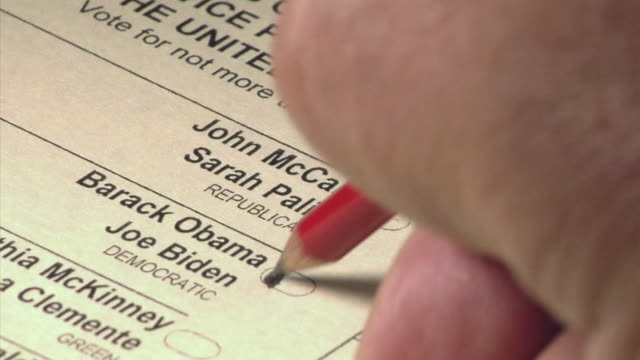 CU hand using pencil to vote for Barack Obama and Joe Biden on US presidential ballot