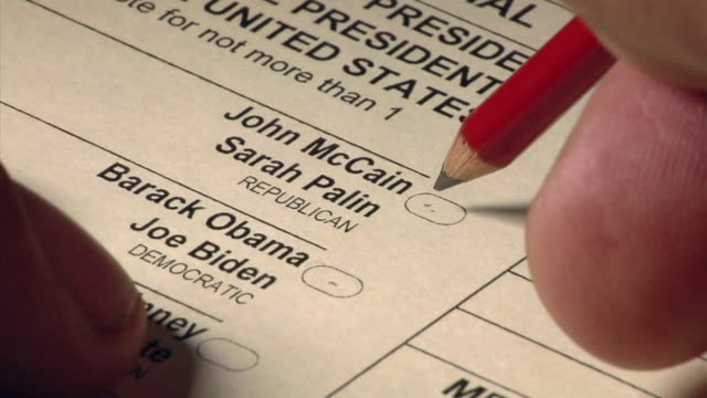 CU hand using pencil to vote for John McCain and Sarah Palin on US presidential ballot / pencil moves between choices before deciding