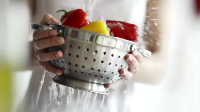 Hand washing peppers, slow motion under a tap   FO