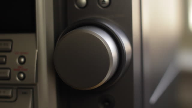 Hand with light complexion turning silver volume knob on stereo up and down