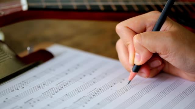 Mano scrivendo note musicali (Dolly shot)