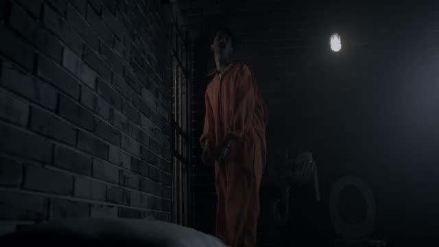 Handcuffed men standing by prison door in prison cell