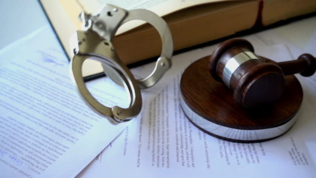 Handcuffs falling onto juridical paperwork contract