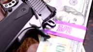 9MM handgun and stacks of $100 bills in $2000 wrappers.