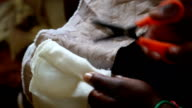 Handheld HA African ethnicity child hand unpicking cotton in sewing class/ KwaZulu-Natal/ South Africa