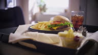 Handheld close up of a lunch tray featuring a cheeseburger, fries and soft drink.