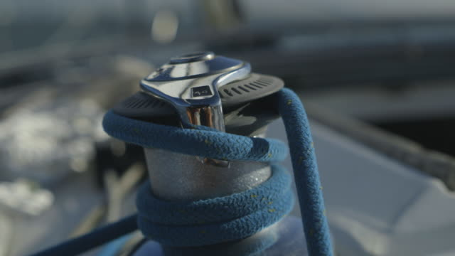 Handheld, close-up shot of a winch on a moving yacht, UK.