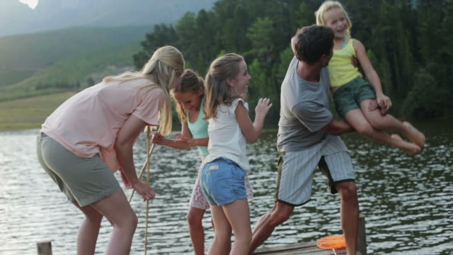 MS handheld of family messing about on jetty by lake