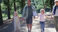 WS MS handheld of family walking along road in forest