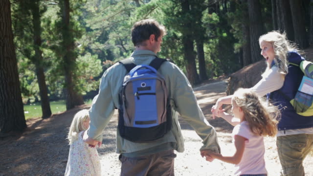 CU MS handheld of family walking along road in forest