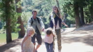 MS handheld of family walking along road in forest