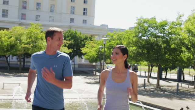 MS handheld of man and woman jogging in city