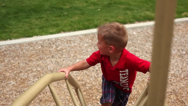 Handheld shot of a little boy at a playground.