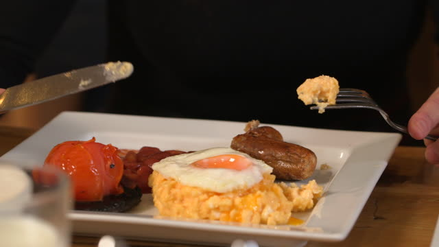 Handheld shot of a person eating a variation of a full English breakfast, UK.