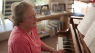 A handheld shot of an senior woman playing the piano.